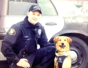Jason Johnson and his police dog Flash by their patrol car